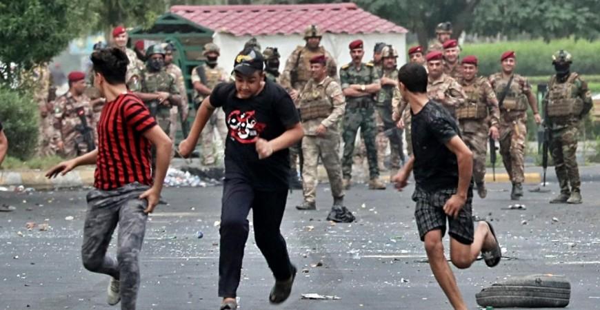 متظاهرون عراقيون يهربون من أما قوات مكافحة الشغب في بغداد (أ. ب.)